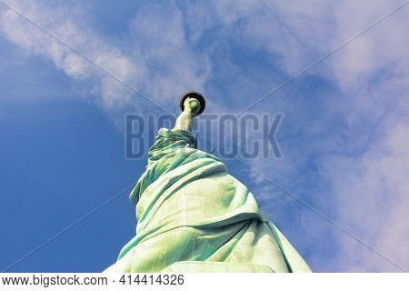 Low angle shot of the Statue of Liberty looking up towards the arm extended with the torch.