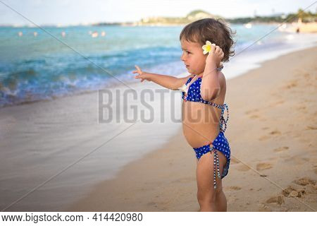 Adorable Toddler Toddler Stands On The Sandy Beach And Points At The Tropical Sea