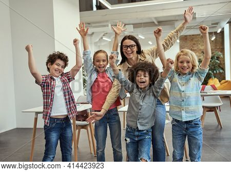 Studying Is Fun. Excited School Team Of Four Happy Little Pupils And Their Cheerful Female Teacher P