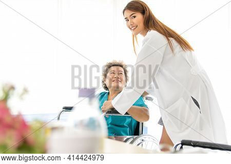 Beautiful Female Doctor Holding The Hand Of A Old Female Patient At A Wheelchair To Encourage The Si