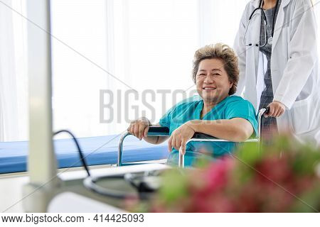 Elderly Female Patients Smiled While Sitting In A Wheelchair, With A Female Doctor Pushing The Wheel