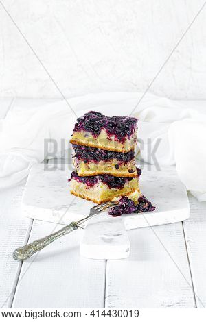 Three Pieces Of Blueberry Cake On A White Marble Cutting Board And White Wood Table