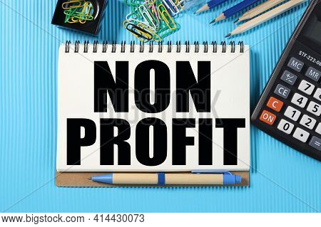 Non Profit. Text On White Notepad Paper On Blue Flask Near Calculator, Paper Clips