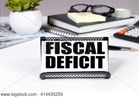 Fiscal Deficit. Text On A White Business Card. Business Card In A Business Card Holder On A Gray Bac