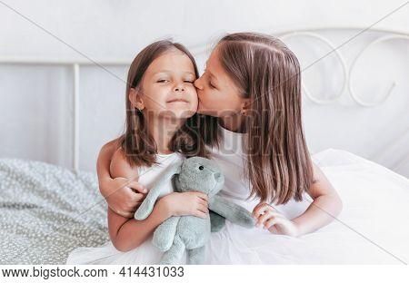 A Little Girl Kisses Her Little Sister On The Cheek. Girls Resting In The Children's Bedroom