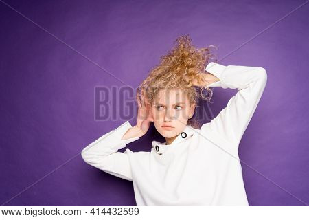Curly-haired Woman Depicts Eavesdropping And Holds Her Ear With Her Hand On A Purple Background