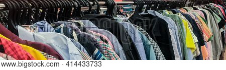 Banner With Row Of Huge Numbers Of Colorful Shirts On Hangers In Second Hand Store. The Concept Of C