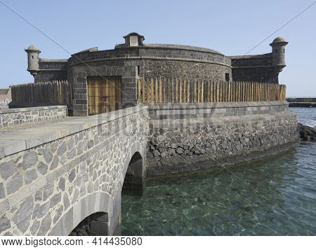 Tenerife, February, 2021: The Black Castle. Defensive Coastal Tower Made Of Basalt Stone, With Two W