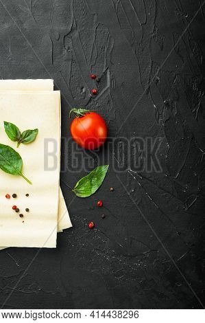 Uncooked Lasagna Sheets Set, With Seasoning And Herb, On Black Stone Background, Top View, Flat Lay,