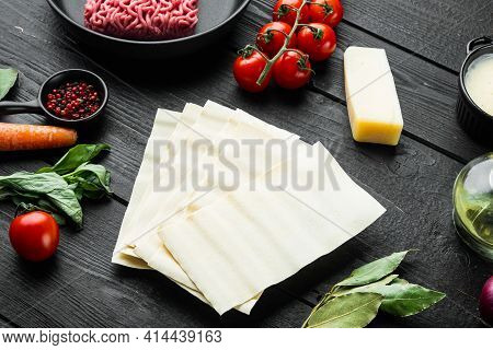 Raw Lasagna Ingredients And Pasta  Set, On Black Wooden Table Background