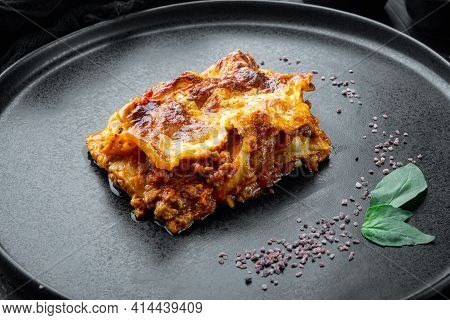 Traditional Lasagna Made With Minced Beef Bolognese Sauce Topped With Basil Leafs Set, On Plate, On