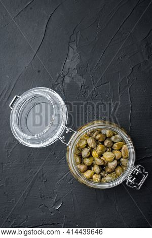 Baby Capers In Glas Jar, On Black Background, Flat Lay  With Copy Space For Text