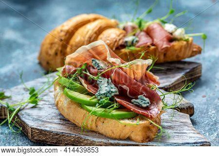 Croissant Sandwich With Jamon Ham Serrano Paleta Iberica, Blue Cheese, Avocado, Microgin On Blue Bac