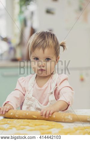 Adorable Baby In An Apron Is Rolling Out The Dough In The Kitchen