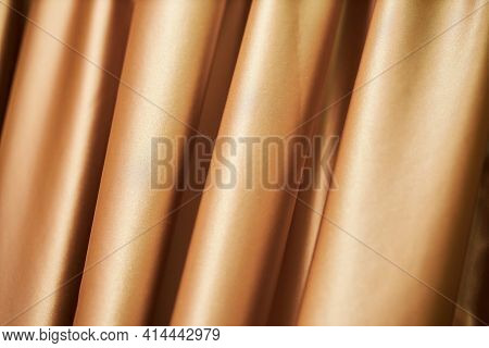 theatrical golden curtain. close-up of golden curtain - photographed, not illustrated. Golden curtain background. Background depicting theater curtain close-up photo
