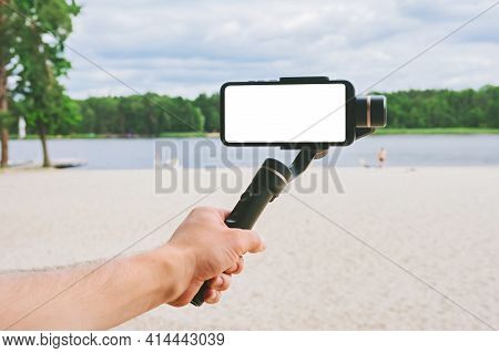 Mock Up Of A Smartphone With A Camera Stabilizer In A Man's Hand. Against The Backdrop Of A Sand Bea