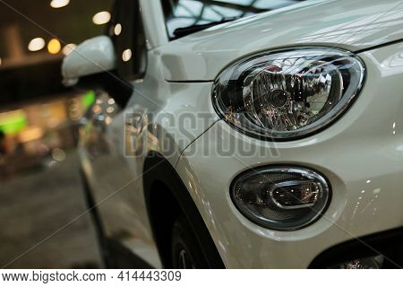 Headlights, white car. headlights of a new white car on a bokeh background. Headlight with LED bulbs and hood of a white modern car. Detail of a car exterior. luxury concept.