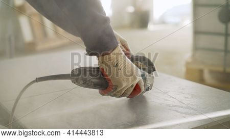 A Man Is Cutting A Ceramic Tile With A Tile Cutter. Worker Cutting A Tile Using An Angle Grinder At