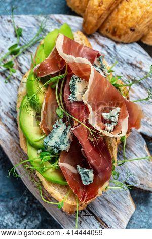 Variety Of Aperitifs Croissant Sandwiches With Jamon Ham Serrano Paleta Iberica, Blue Cheese, Avocad