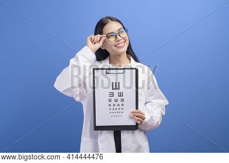 Young Female Ophthalmologist With Glasses Holding Eye Chart Over Blue Background Studio, Healthcare