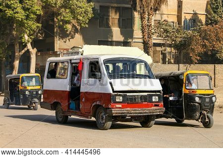 Giza, Egypt - January 26, 2021: Small City Minibus Eltramco Ramzes And Auto Rickshaws Bajaj Re In Th