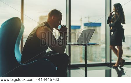 A Pensive Mature Caucasian Man Entrepreneur Sitting On A Teal Armchair In Front Of His Laptop In Fro