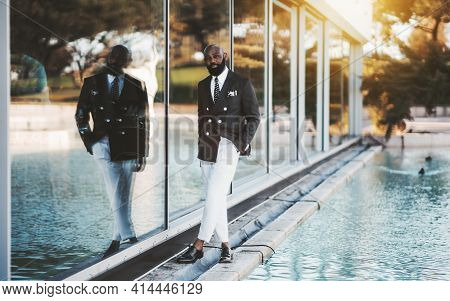 A Stately Mature Bearded Bald Black Guy In An Elegant Costume With White Trousers Is Standing On The