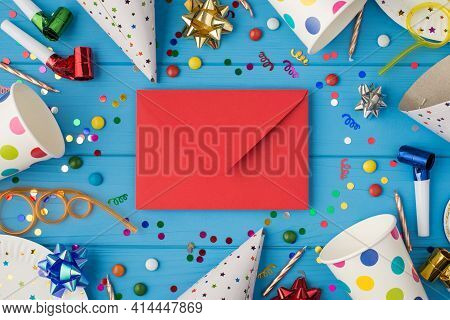 Top View Photo Of Birthday Party Composition Closed Red Envelope In The Middle Spiral Tubes Ribbon S