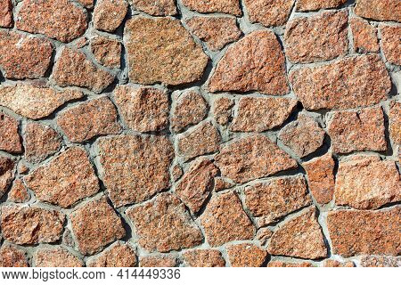 The Texture Wall Of Red Granite And The Background In The Form Of Large Blocks Embedded In The Wall