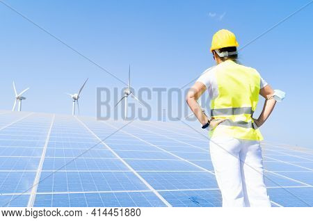 Alternative Energy Concept - Back Of Woman In Covid Mask Standing In Front Of Solar Panels, Green En