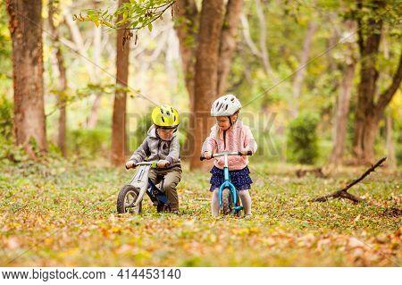 Cheerful Preschool Kids Outdoors On Balance Bikes