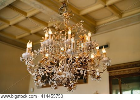 Crystal Chandelier With Candles In A Floral Style In The Interior Of A Villa In Italy.