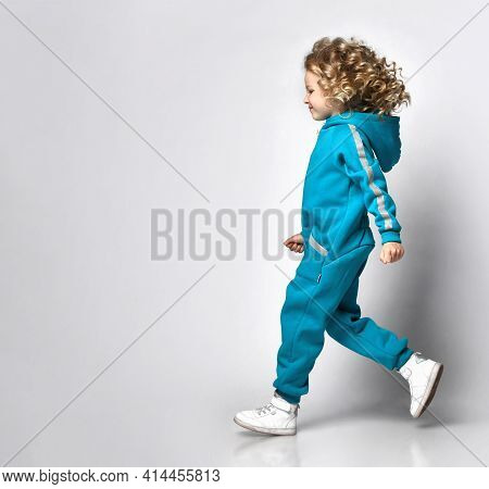 Running Active Girl In A Warm Fashionable Overalls, Fashionable Comfortable Sportswear And Sneakers