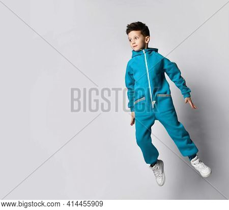 Cheerful Boy In A Sports Suit Jumps High. Schoolboy Advertises Sports Outerwear. Sporty Fashionable