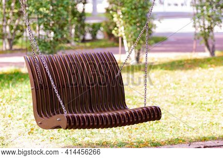 A Bench Suspended By Chains. Air Bench Made Of Wooden Parts. Summer And A Tempting Shade On The Benc