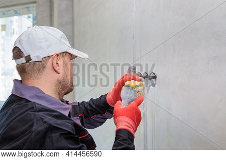 An Electrician Drills Holes For Sockets With A Diamond Core Bit