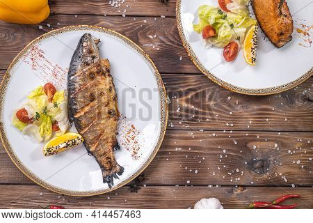 Grilled Fish On A Plate With Vegetables, Bell Pepper, Coarse Salt On A Brown Wooden Background. Rest