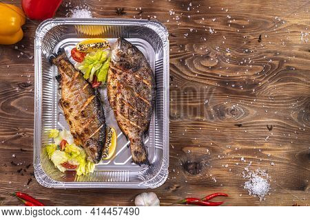 Grilled Fish With Vegetables, Bell Pepper, Coarse Salt, Laid In An Aluminum Container On A Brown Woo