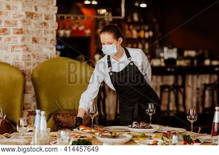 Young Female Waiter In Uniform With Medical Mask And Gloves Serving In The Restaurant. Copy Space.