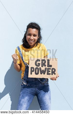 Portrait Of A Latin Woman Holding A Banner With Girl Power Slogan. She Is Isolated On Blue Backgroun