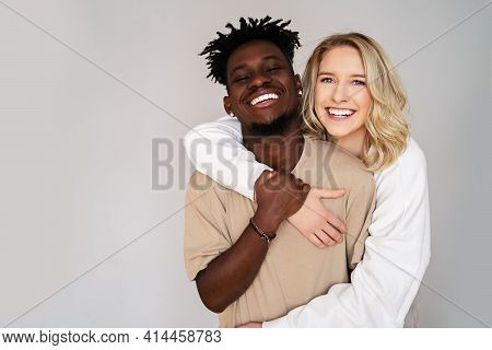 A Beautiful Black Young Man With Dreadlocks And A Young Blue-eyed Blonde Woman Hug And Laugh On A Gr