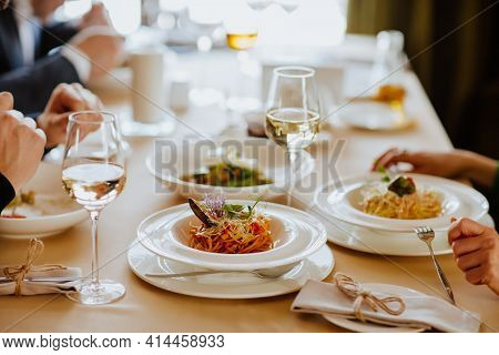 Lunch Tablecloth With White Wine And Spaghetti In Restaurant.