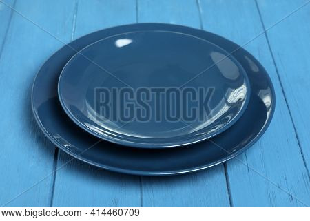 Empty Clean Ceramic Dishware On Blue Wooden Table, Closeup