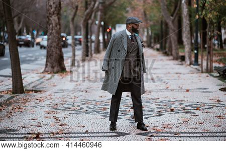 A Dapper Mature African Senior With A Black Well-groomed Beard Is Standing In The Middle Of An Autum
