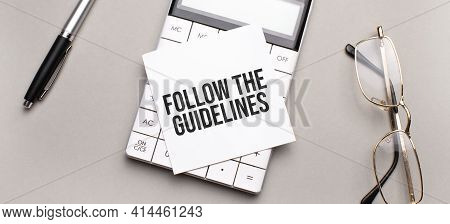 Pen, Calculator And Glasses On Grey Background. Business Concept. White Paper Sheet With Follow The