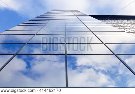 View Of A Modern Glass Skyscraper. Reflection Of A Cloudy Blue Sky In A Glass Skyscraper