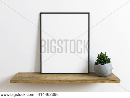 Black Frame Mockup On Wooden Shelf With Green Plant In A Vase And White Wall Behind It. Empty Poster