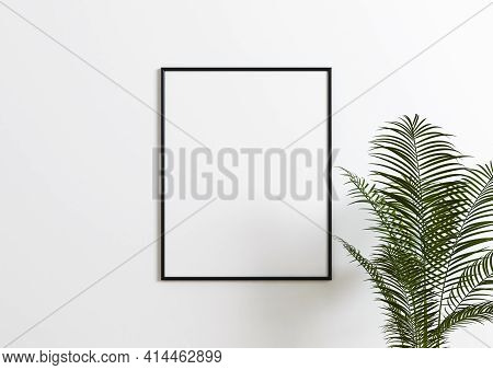 Black Frame Mockup With Green Plant And White Wall Behind It. Empty Poster Frame Mockup With Plant.