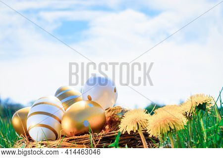 Easter Basket With Eggs. Golden Egg With Yellow Spring Flowers In Celebration Basket On Green Grass