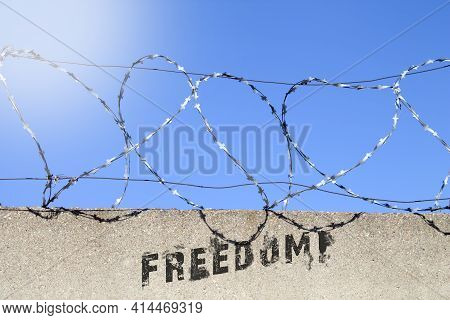 Freedom Inscription On The Wall With Barbed Wire. Protests For The Freedom Of The Prisoner. Graffiti
